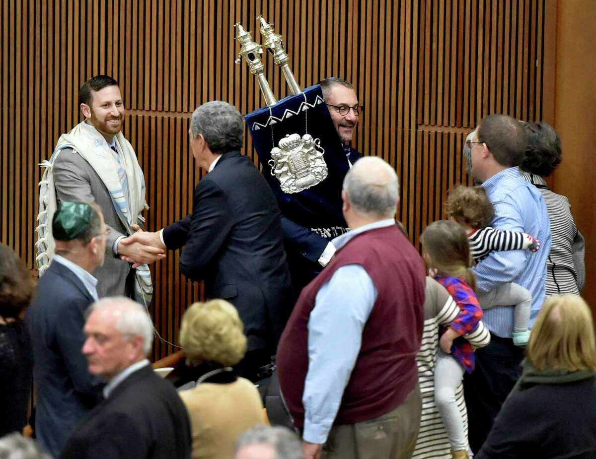 In this file photo, Rabbi Brian Immerman, left, in 2018 greets people during the Hakafa with Rabbi Joe Black of Temple Emmanuel of Colorado, right, carrying the Torah during Immerman's installation ceremony as the new rabbi of Congregation Mishkan Israel.