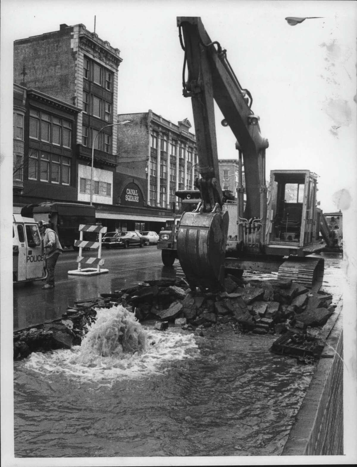 State Street at Jay, Schenectady, New York - This large shovel tearing up the pavement on the north side of State Street got more than he bargained for as he also tore up a water pipe in the process, filling up the ditch with water. The sign on the building across the street says Canal Square - maybe they'll make it a canal instead. April 4, 1984 (Paul D. Kniskern Sr./Times Union Archive)