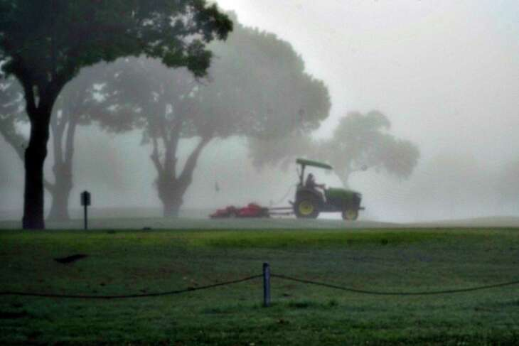 A groundskeeper is seen through the dense fog as he maintains the greens and fairways at Olmos Basin Golf Course on March 25, 2020. Wednesday was the first day of the shleter at home directive issued in San Antonio,