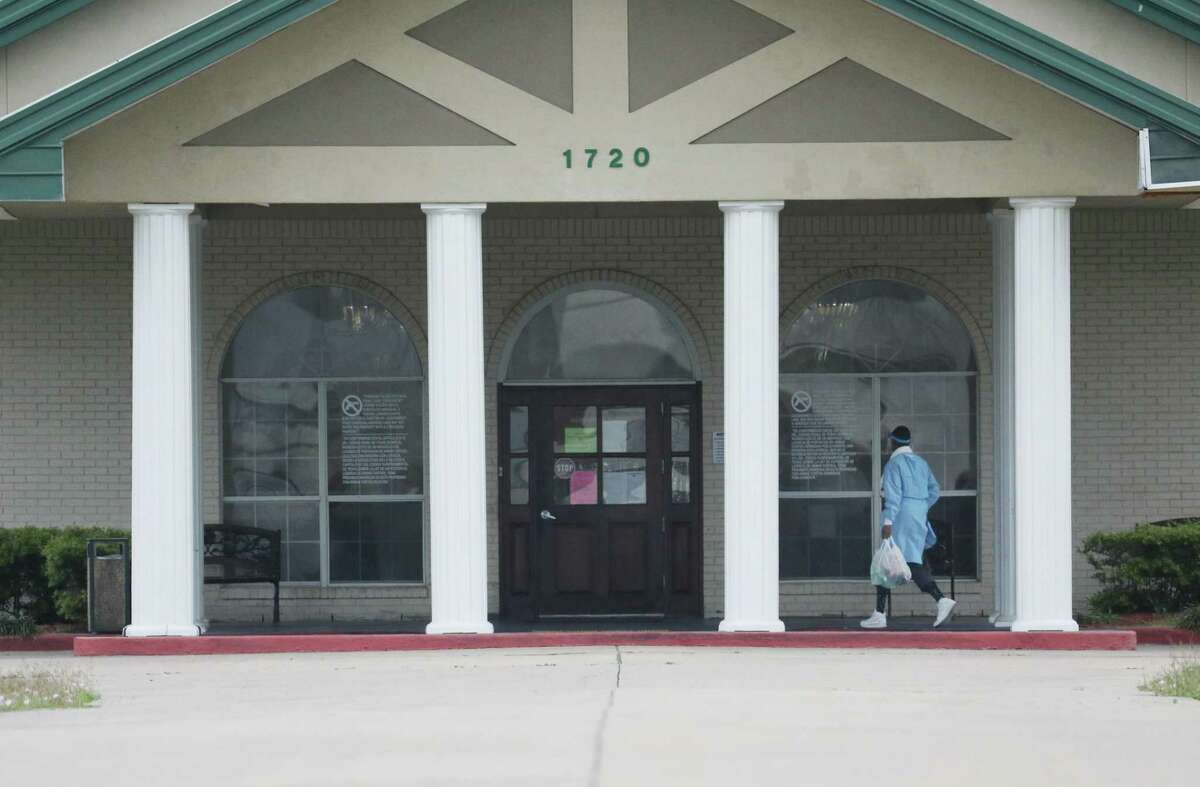 A person wearing PPE walks into The Resort at Texas City, a nursing home where 80 residents and employees tested positive for the new coronavirus, on Friday, April 3, 2020, in Texas City.