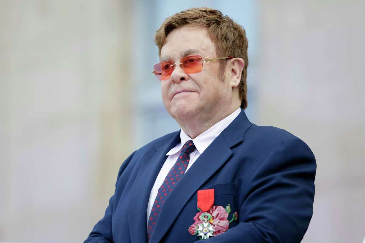 FILE - This June 21, 2019 file photo shows Elton John at a ceremony honoring him with the Legion of Honor in Paris. John is hosting a a€œliving rooma€ concert aimed at bolstering American spirits during the coronavirus crisis and saluting those countering it. The event was announced Wednesday by iHeartMedia and Fox. Alicia Keys, Billie Eilish, Mariah Carey, the Backstreet Boys, Tim McGraw and Billie Joe Armstrong are scheduled to take part in the concert airing at 9-10 p.m. Eastern Sunday on Fox TV and on iHeartMedia radio stations. (AP Photo/Lewis Joly, Pool, File)