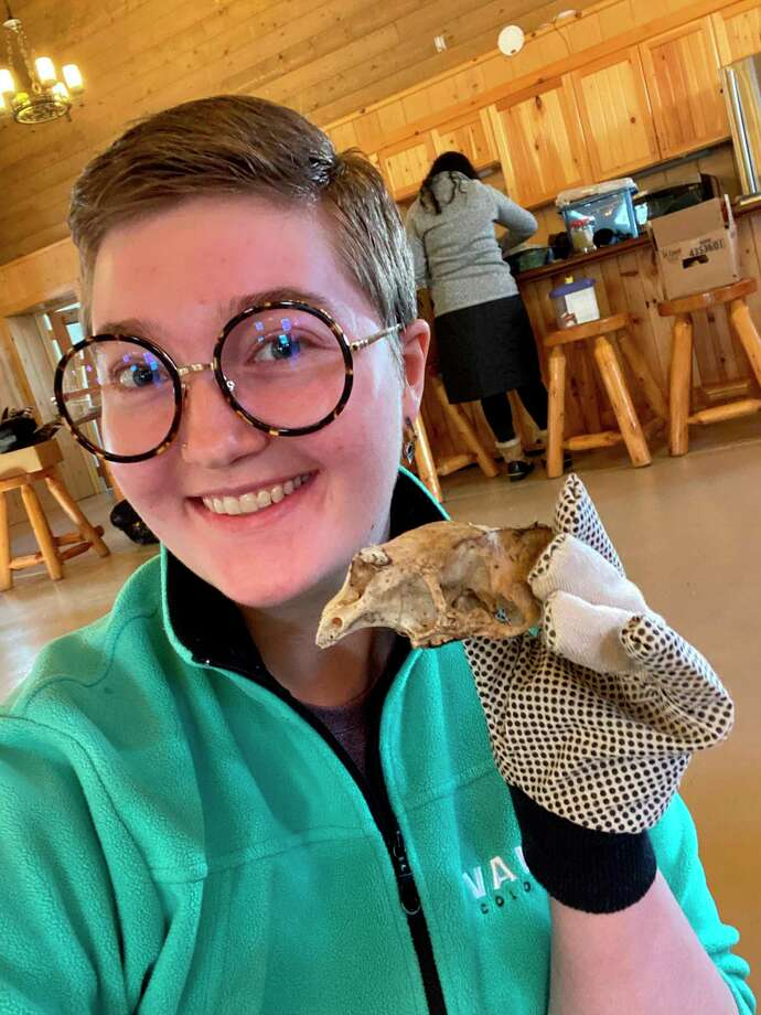 Story author Emma Kukuk poses for a photo with the skull of a road-killed porcupine she cleaned. (Michigan DNR/Courtesy Photo)