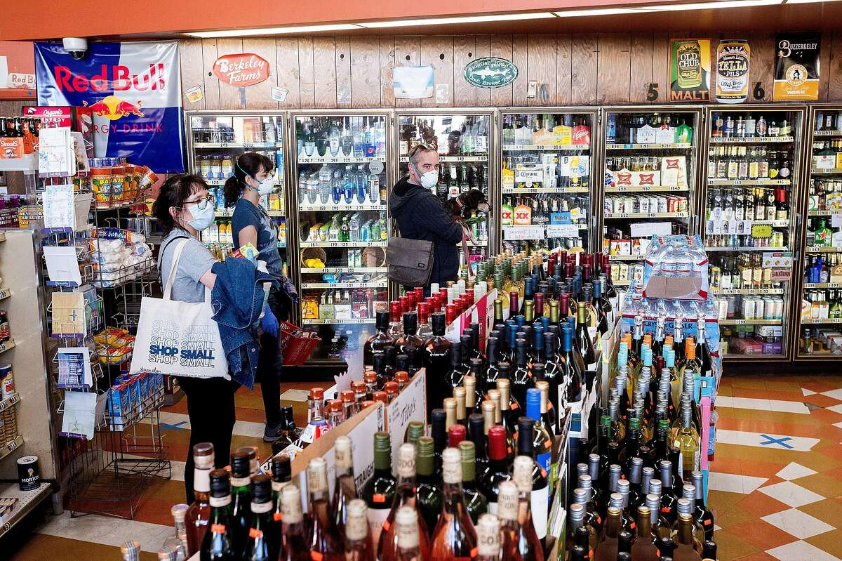 Customers shop for alcohol at Eddie's Drive In Liquors in Oakland, Calif., on Friday, April 3, 2020. The store maintains brisk business despite shelter-in-place orders enacted to slow the spread of coronavirus.