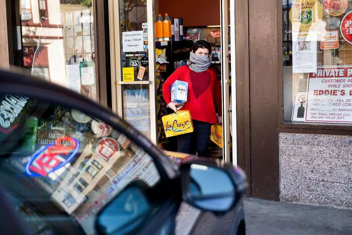 Anne Butterfield carries beer and sparkling water drinks during a shopping trip to Eddie's Drive In Liquors in Oakland, Calif., on Friday, April 3, 2020. The store maintains brisk business despite shelter-in-place orders enacted to slow the spread of coronavirus.