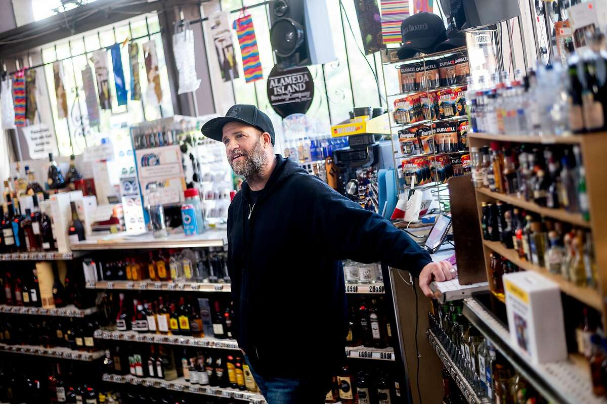 Store manager Adam Johnson works the counter at Eddie's Drive In Liquors in Oakland, Calif., store on Friday, April 3, 2020. The store maintains brisk business despite shelter-in-place orders enacted to slow the spread of coronavirus.