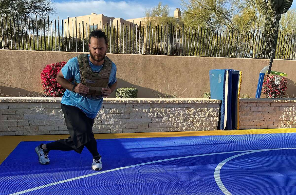 Brandon Crawford of the San Francisco Giants performs lunges while wearing a weighted vest at his Arizona home.