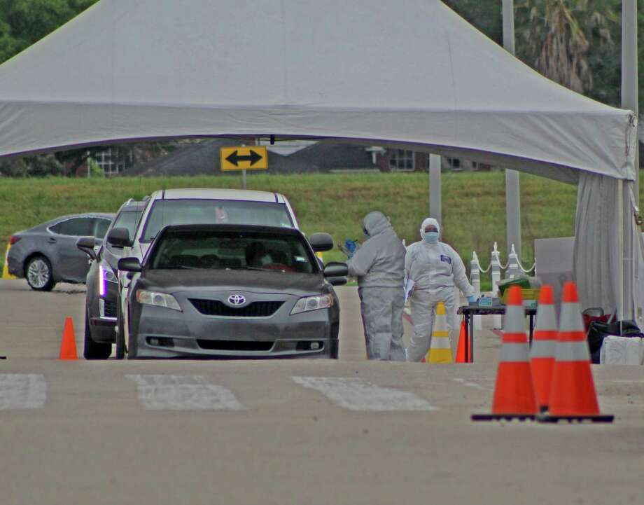 Medical workers administer COVID-19 tests at a drive-through testing site outside Sugar Land's Smart Financial Center on Friday, APril 3. Photo: Kristi Nix
