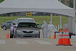 Medical workers administer COVID-19 tests at a drive-through testing site outside Sugar Land's Smart Financial Center on Friday, April 3.