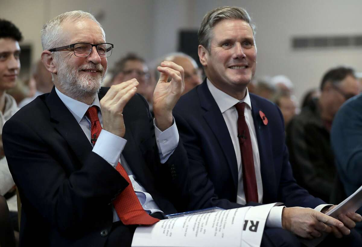 FILE - In this Tuesday, Nov. 5, 2019 file photo, Britain's opposition Labour party leader Jeremy Corbyn, left, and Keir Starmer Labour's Shadow Secretary of State for Exiting the European Union applaud Labour Prospective Parliamentary Candidate for Harlow Laura McAlpine's speech during their election campaign event on Brexit in Harlow, England. Britain's main opposition Labour Party has elected lawyer and lawmaker Keir Starmer as its new leader, after a contest thrown into turmoil by the coronavirus outbreak, it was announced on Saturday, April 4, 2020. (AP Photo/Matt Dunham, File)