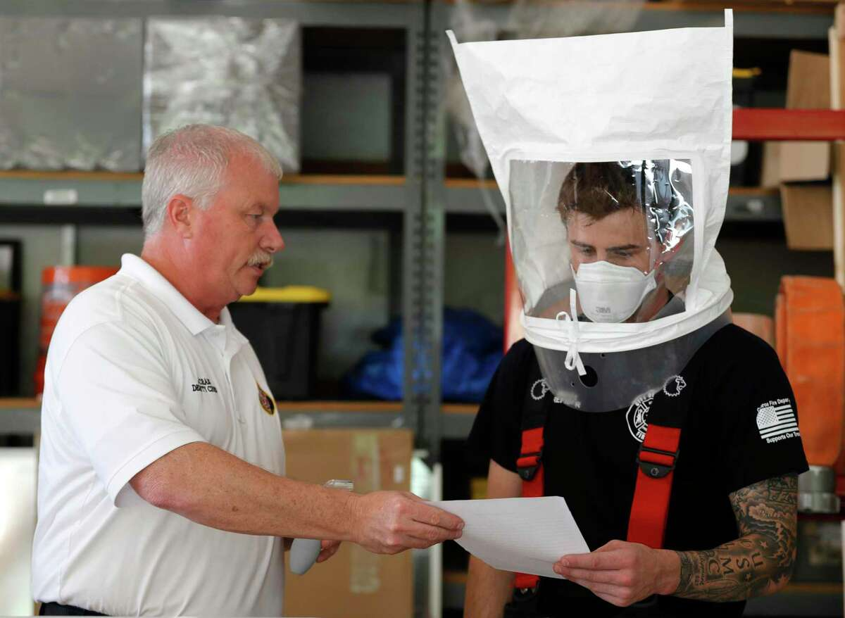 Conroe Fire Department Deputy Chief Joe Craig, left, hands firefighter Tyler Wagner a document to read as part of the fitting process as firefighters are issued 3M N95 mask, Tuesday, March 31, 2020, in Conroe.