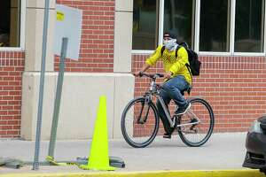 A man covers his face as he rides his bike, Friday, April 3, 2020, in downtown Houston.