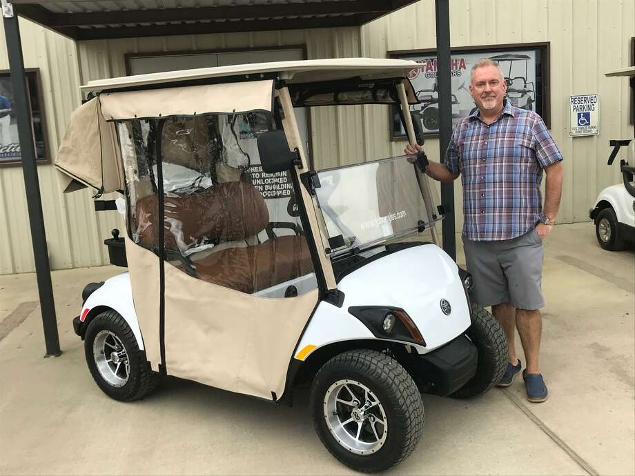 Chris Delussey, owner of Action Buggies, is shown with the Yamaha golf cart that will be offered as a hole-in-one prize. Photo: Courtesy Photo