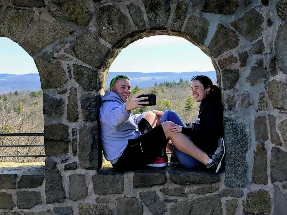 Two people enjoy a photo on the castle at the top of Sleeping Giant State Park. Photo: Joe Amarante / Hearst Connecticut Media