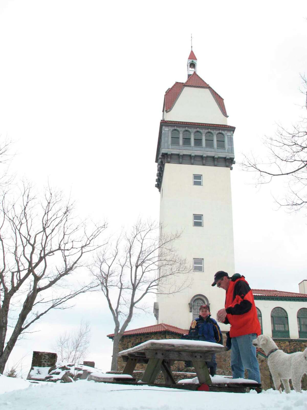 Simsbury_031305 Roger Potter, right, his son, Wilson, 5, and their standard poodle, Gordie, stop to eat at the top of Talcott Mountain next to Heublein Tower at Talcott State Park in Bloomfield on Sunday. The tower was built as a summer home for Gilbert Heublein in 1914, and offers a 1,000 high view of the Farmington River Valley. Chris Preovolos/Staff Photo CT View