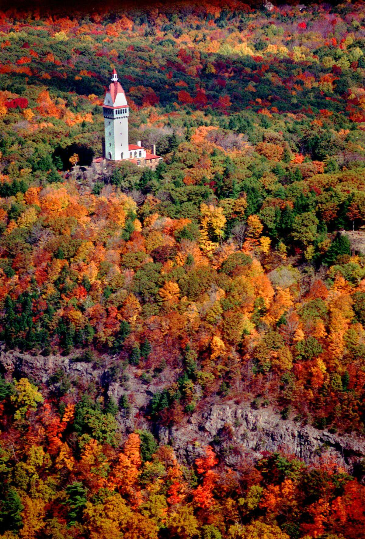 Autumn foliage is at its peak Tuesday, Oct. 19, 1999, surrounding the Hueblein Tower on the top of the Talcott Mountain State Park in Simsbury, Conn., as seen in this aerial photo. (AP Photo/The Hartford Courant, Alan Chaniewski)