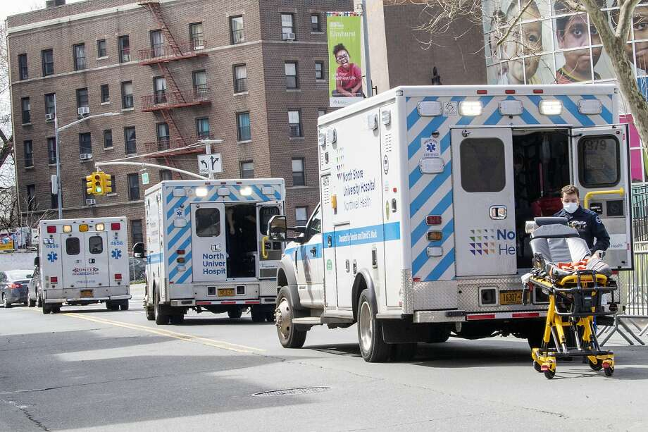 Ambulances line the street outside Elmhurst Hospital Center, Saturday, April 4, 2020 in the Queens borough of New York. The new coronavirus causes mild or moderate symptoms for most people, but for some, especially older adults and people with existing health problems, it can cause more severe illness or death. (AP Photo/Mary Altaffer) Photo: Mary Altaffer / Associated Press