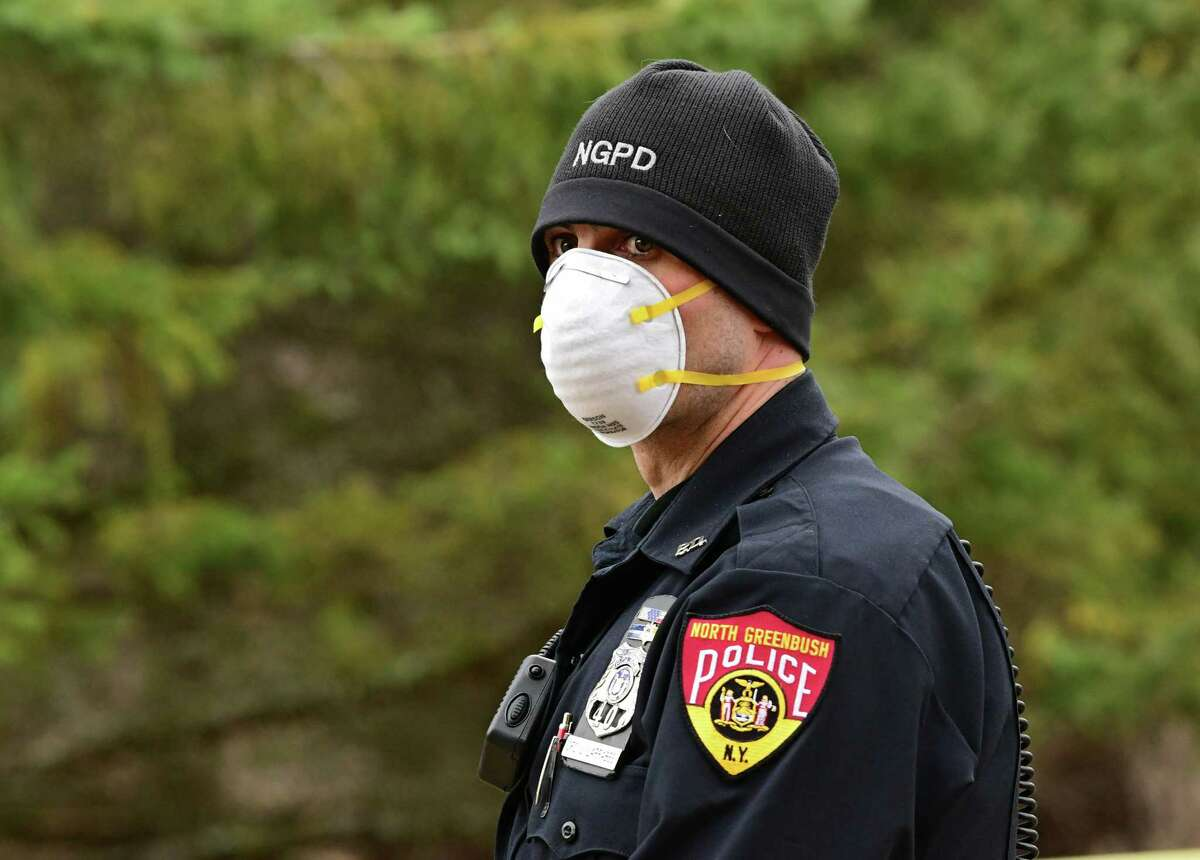 A police officer is seen wearing a protective face mask at the scene of a house fire on Scythe Lane on Tuesday, March 31, 2020 in North Greenbush, N.Y. (Lori Van Buren/Times Union)