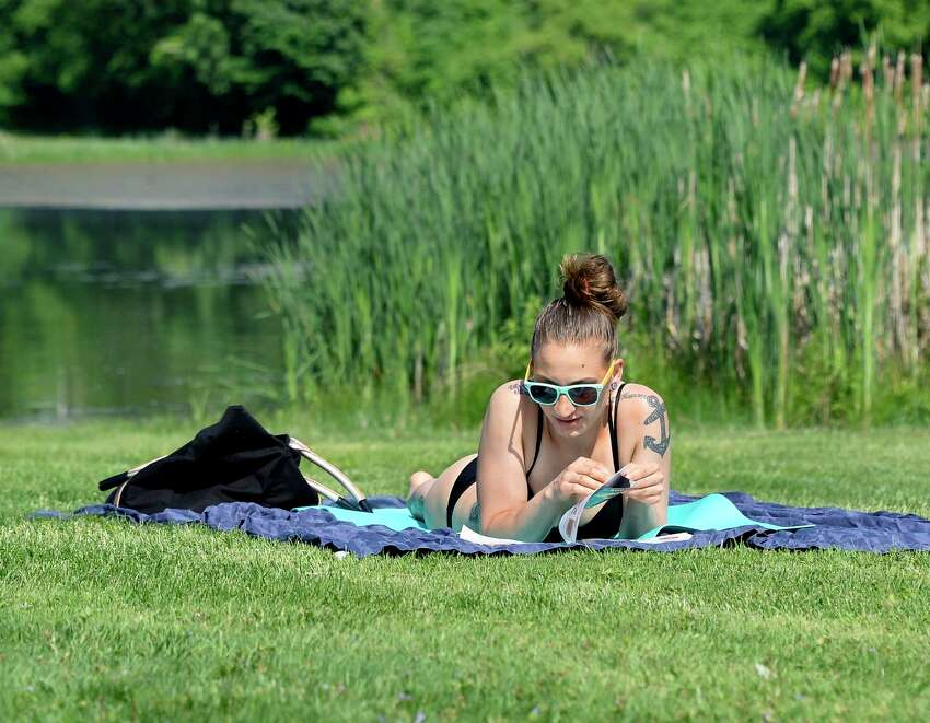 Jennifer Smaltz of Scotia catches up on her reading while catching some rays at Collins Park Wednesday May 30, 2018 in Scotia, NY. (John Carl D'Annibale/Times Union)