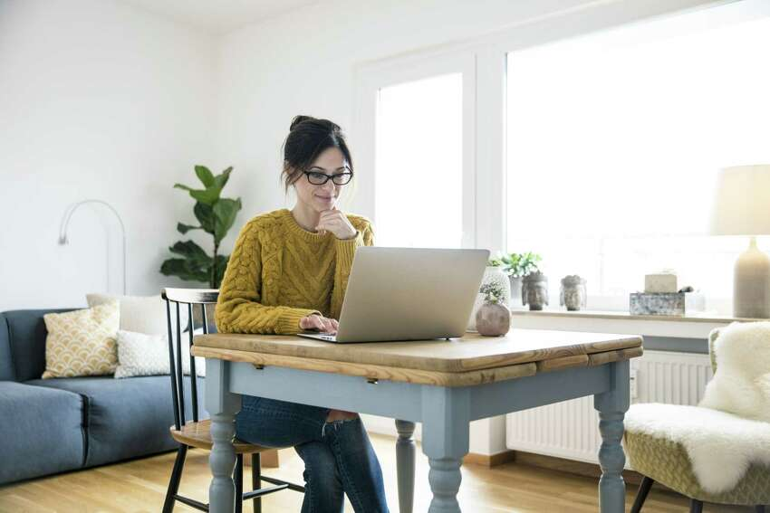 Woman sitting at table, using laptop. (Getty Images)