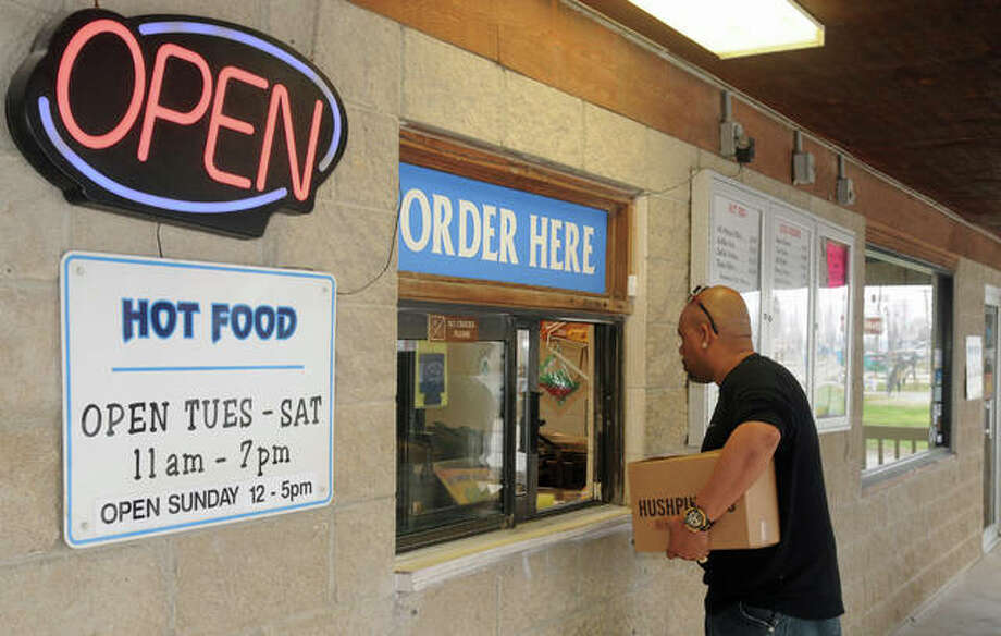 "Lamont Starks of Florissant, Missouri, places a carry-out order at Beasley Fish Stand in Grafton. ""Here in Grafton, everybody pulls together. It's a wonderful community for helping each other,"" said owner Deborah Beasley."