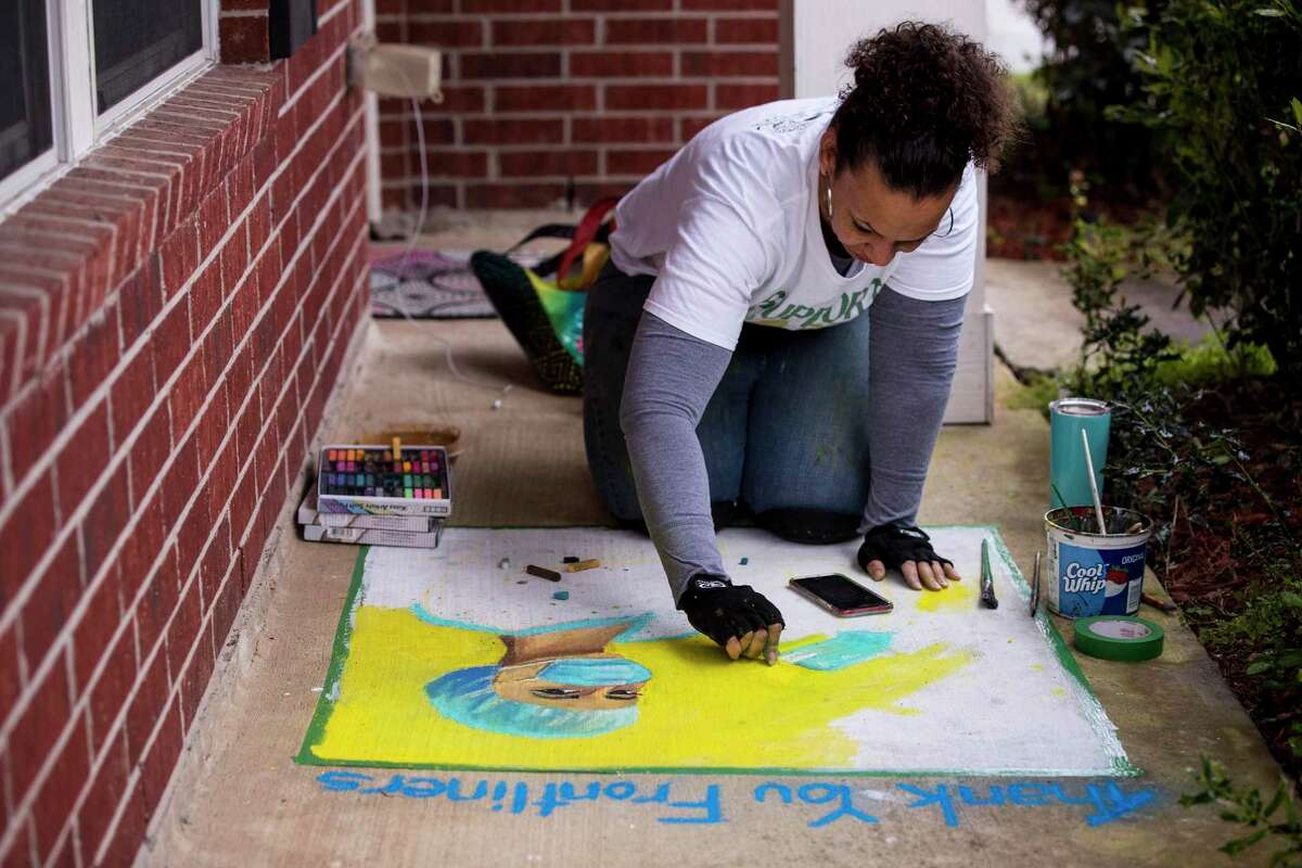 """Lauren Luna works a piece of chalk art, thanking front line medical workers, on her front porch on Saturday, April 4, 2020 in Houston. Luna was originally scheduled to teach a class and produce a giant art installation of a game of Twister, in connection with a Midtown Houston artist event, in Baldwin Park. """"But instead I'm hanging out at home doing a virtual Chalk the Block,"""" she said."""