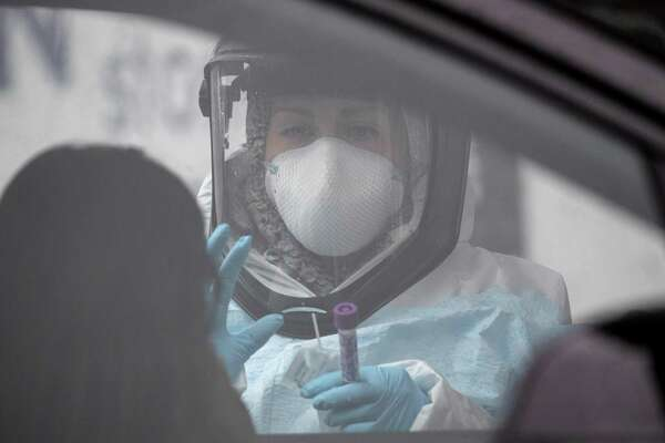 A nurse, dressed in personal protective equipment (PPE) prepares to give a coronavirus swab test at a drive-thru testing station at Cummings Park on March 23, 2020 in Stamford, Connecticut. Availability of protective clothing for medical workers has become a major issue as COVID-19 cases surge throughout the United States. The Stamford site is run by Murphy Medical Associates.