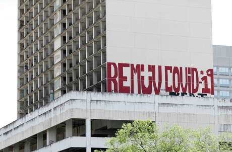 "A new mural on the side of an abandoned building that reads ""Remuv Covid-19"" downtown, in Houston, Sunday, March 29, 2020."