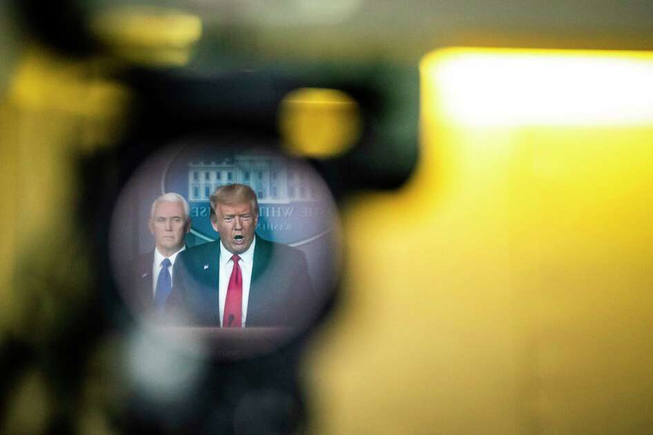 President Trump, reflected in a television camera, speaks with his coronavirus task force at a White House briefing on March 18., 2020.