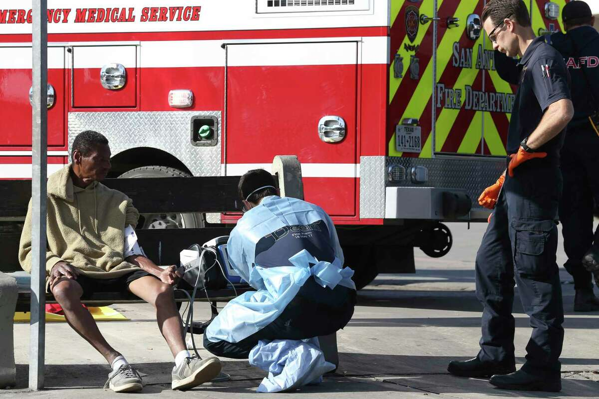 San Antonio Fire Department personnel treat a man at the intersection of McCullough Avenue and Ashby Place on Tuesday, March 31, 2020. Emergency personnel take extra precautions - such as wearing personal protection equipment - due to the coronavirus pandemic. The man was checked out and released.