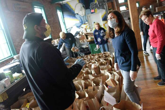 TAG driver Ron Culver and volunteer Connie Figgie pack up meals to be distributed at the new temporary location of Neighbor to Neighbor's food pantry at the Arch Street Teen Center in Greenwich, Conn. Tuesday, March 31, 2020. The Neighbor to Neighbor nonprofit moved its food pantry to the Arch Street Teen Center for a larger workspace that allows for social distancing during the coronavirus outbreak.