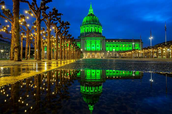 City Hall is lit green for the 150th anniversary of Golden Gate Park on Saturday, April 4, 2020, in San Francisco, Calif. The building is seen reflected off a pond that formed from earlier rain.