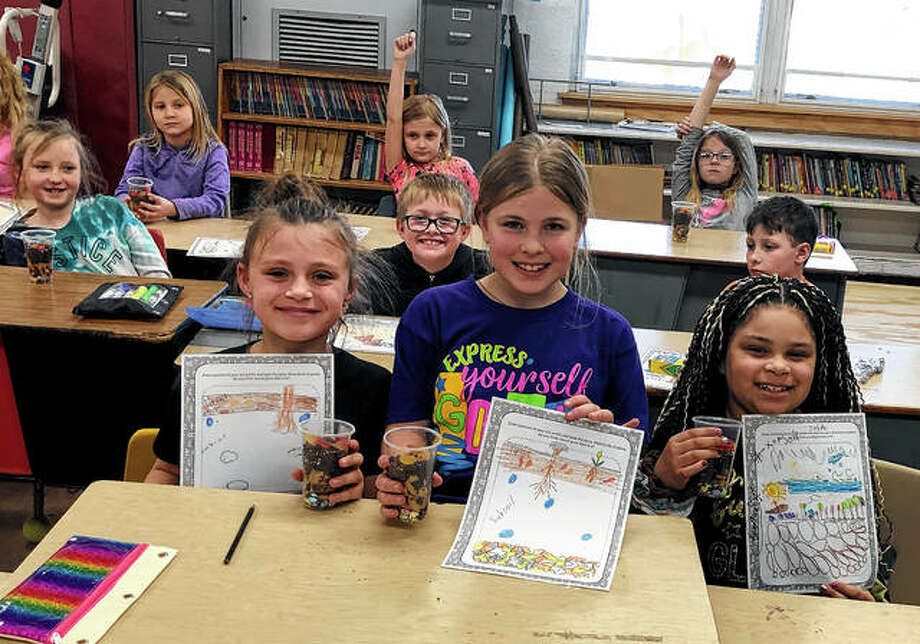 "The Pike-Scott Agriculture in the Classroom program recently visited Griggsville-Perry Elementary School to teach students about soil. With some help from Griggsville-Perry High School FFA student volunteer Tyler Dejaynes, students learned about the layers of soil — topsoil, subsoil and bedrock — and the differences in each. Students displayed their edible ""soil"" snacks and their soil profile drawings. Photo: Photo Provided"