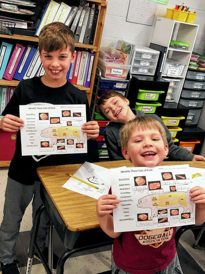 The Pike-Scott Agriculture in the Classroom program recently visited Winchester Elementary School to teach its third-graders about pigs through a video and some hands-on activities. Mrs. Leonard's students Nate Merritt (front), Emerson Little (back left) and Carter Stice show their work on their pork-themed worksheets. Photo: Photo Provided