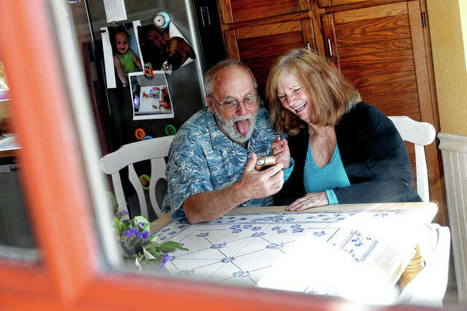 Seen through their kitchen window, Allan and Debbie Cameron of Chandler, Arizona, contact their grandchildren March 25 via the internet. Debbie, 68, has asthma, which makes her one of the people most at risk from the new coronavirus. The Camerons now see their children and grandchildren from the other side of a window or a phone. Photo: Matt York | Associated Press