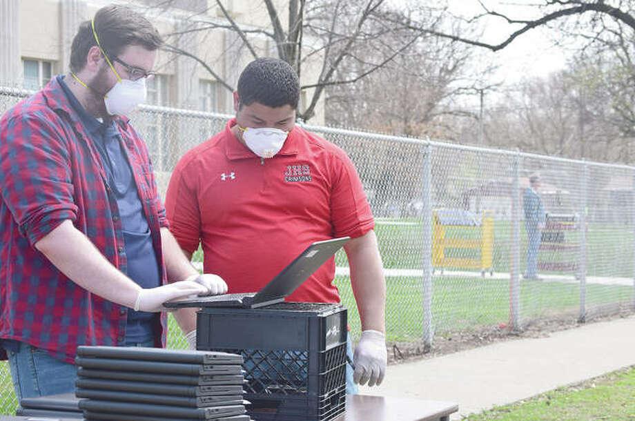 Logan Tannahill (left) and Javonn Gardner of Jacksonville School District 117's technology department prepare laptops for student pickup outside Washington Elementary School. Photo: Samantha McDaniel-Ogletree | Journal-Courier