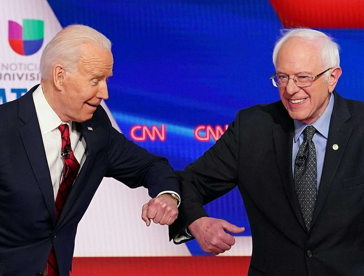 (FILES) In this file photo taken on March 15, 2020 Democratic presidential hopefuls former US vice president Joe Biden (L) and Senator Bernie Sanders greet each other with a safe elbow bump before the start of the 11th Democratic Party 2020 presidential debate in a CNN Washington Bureau studio in Washington, DC on March 15, 2020. - Three weeks ago, Joe Biden and rival Bernie Sanders were hosting rallies that attracted thousands. The pair often visited two states a day in their fierce and spirited battle for votes. Today, they appear online as lonely candidates hunkered down in their homes, forced off the trail and into campaign reinvention mode as the intensifying coronavirus pandemic upends the Democratic presidential primaries along with every other aspect of American life. (Photo by Mandel NGAN / AFP) (Photo by MANDEL NGAN/AFP via Getty Images)