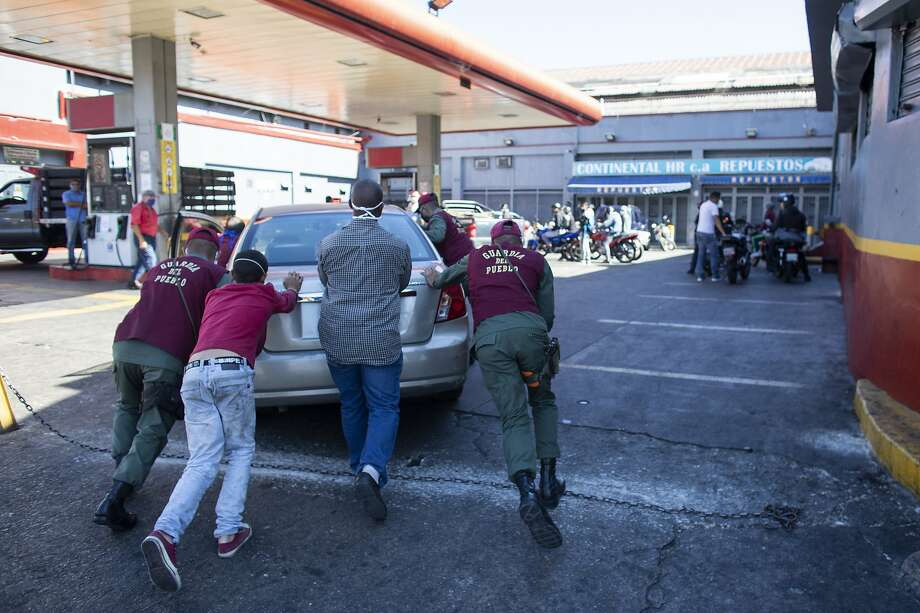Bolivarian National Guard members help push a car into the gas station during the second week of the national quarantine on March 27, 2020 in Caracas, Venezuela. Photo: Leonardo Fernandez Viloria / Getty Images