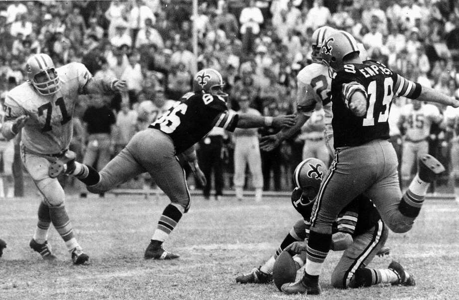 FILE - In this Nov. 8, 1970, file photo, New Orleans Saints' Tom Dempsey (19) moves up to kick a 63-yard field goal as teammate Joe Scarpati holds the ball and Detroit Lions' Alex Karras (71) rushes in while Saints' Bill Cody (66) blocks, in New Orleans. Dempsey, who played in the NFL despite being born without toes on his kicking foot and made a record 63-yard field goal, died late Saturday, April 4, 2020, in New Orleans while struggling with complications from the new coronavirus, his daughter said. He was 73 years old. (AP Photo/File) Photo: Associated Press