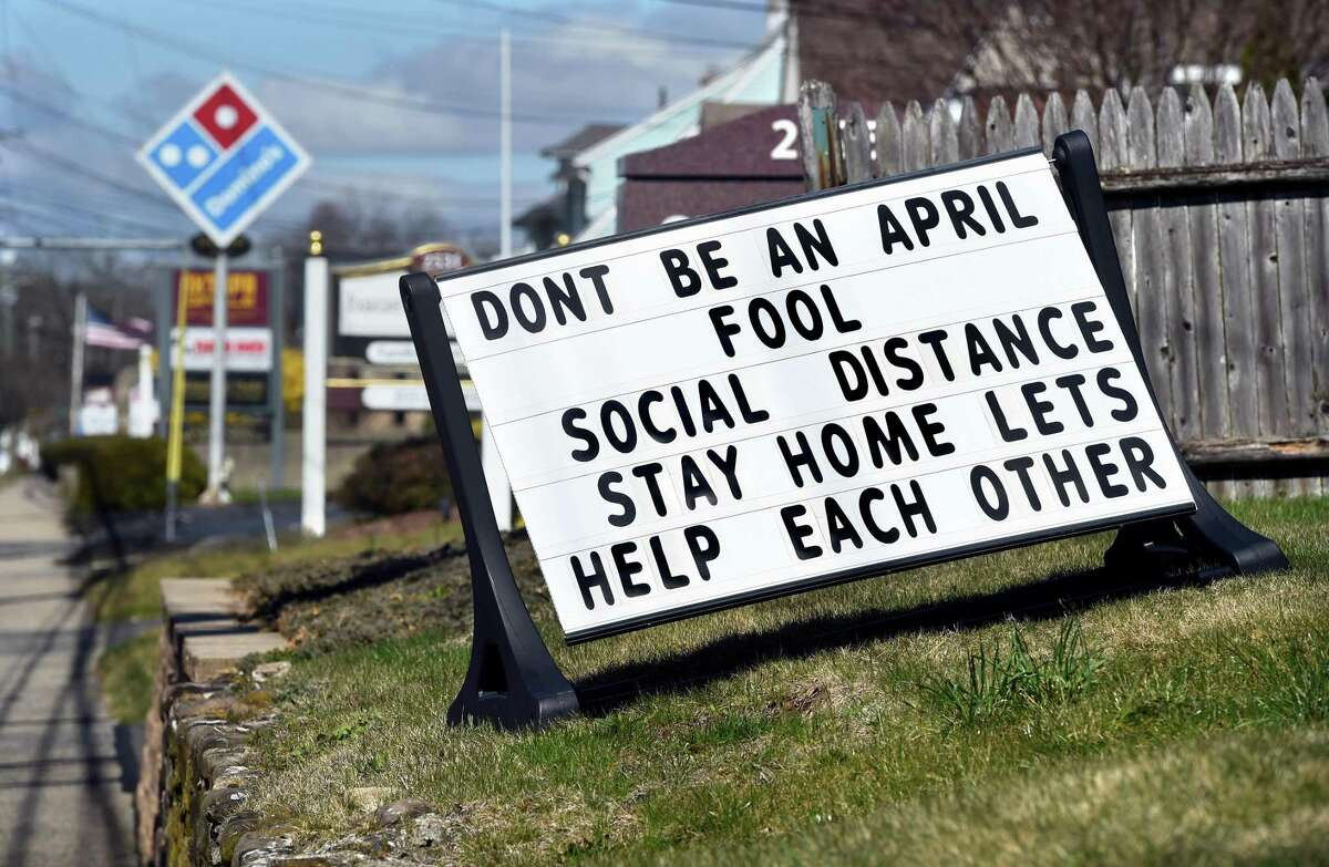 A sign promoting social distancing is displayed on Whitney Avenue in Hamden on April 4, 2020.