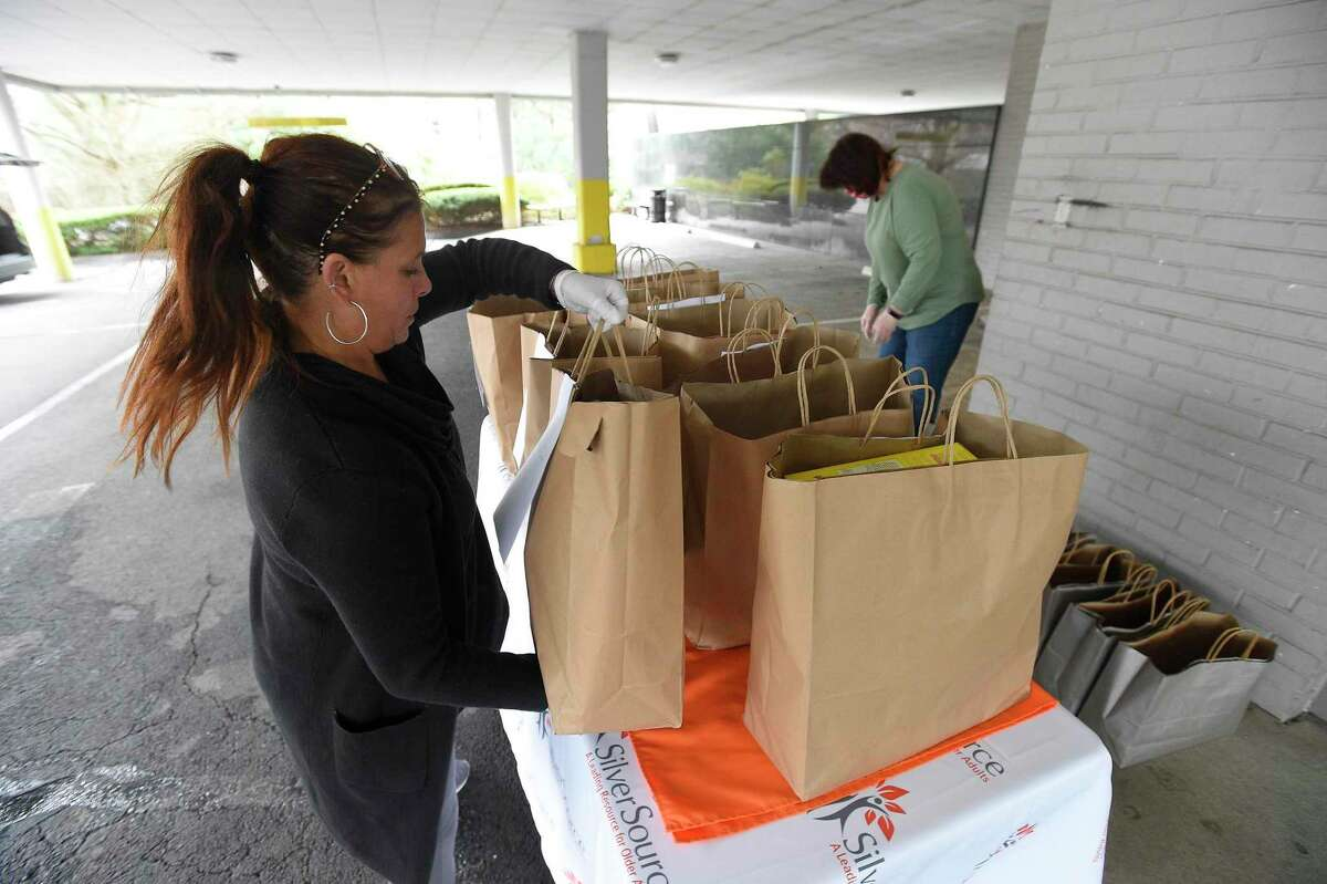 Volunteer Kimberly Wood of Redding checks bags of groceries as volunteers get ready to make deliveries to clients of SilverSource on March 31, 2020 in Stamford, Connecticut. Wood and several volunteers of SilverSource provided a safety net to older residents in need, by making food deliveries, picking up medications or simply checking in on them by calling and having a client come to the window or door as they wave from the sidewalk in a socially acceptable distance. Many seniors are fearful to get out to get food or medications and rely on the kindness of others, as they shelter in place in response to the COVID-19 crisis.