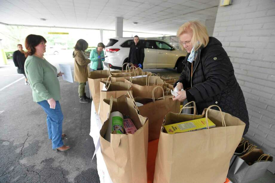 Kathleen Bordelon, executive director of SilverSource, double checks bags of groceries as she works with a group of volunteers preparing to make food and essential items deliveries to elderly residents in the area on March 31, 2020 in Stamford. Photo: Matthew Brown / Hearst Connecticut Media / Stamford Advocate