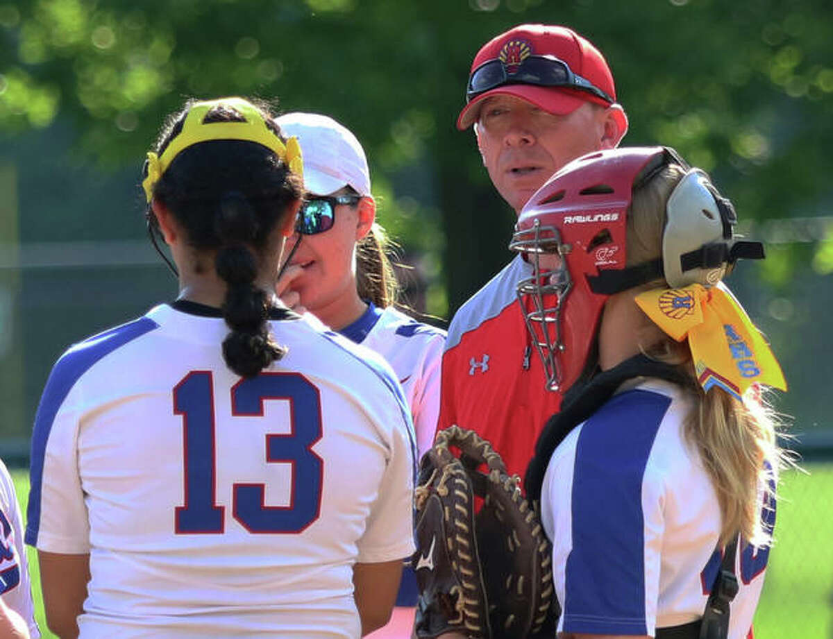 Roxana coach Wade Stahlhut (back, right) huddles with some Shells in the pitcher's circle during a game last year in his first season as head coach.