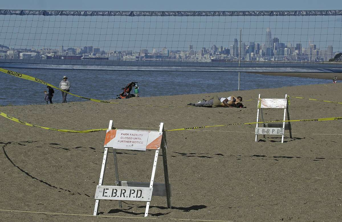 People are seen near a volleyball net that has been closed by the East Bay Regional Park District during the COVID-19 outbreak at Robert W. Crown Memorial State Beach, Thursday, March 26, 2020, in Alameda, Calif. The new coronavirus causes mild or moderate symptoms for most people, but for some, especially older adults and people with existing health problems, it can cause more severe illness or death. (AP Photo/Ben Margot)