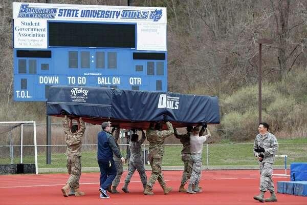 Connecticut Air and Army National Guard personnel move pole vault and high-jump mats to an outdoor field to make room inside Moore Field House for a temporary field hospital to be constructed to the current coronavirus crisis at Southern Connecticut State University, Tuesday, March 31, 2020, in New Haven, Conn. The 250-bed field hospital will facilitate overflow in the event that regional hospitals treating COVID-19 patients reach their capacity. (AP Photo/Kathy Willens)