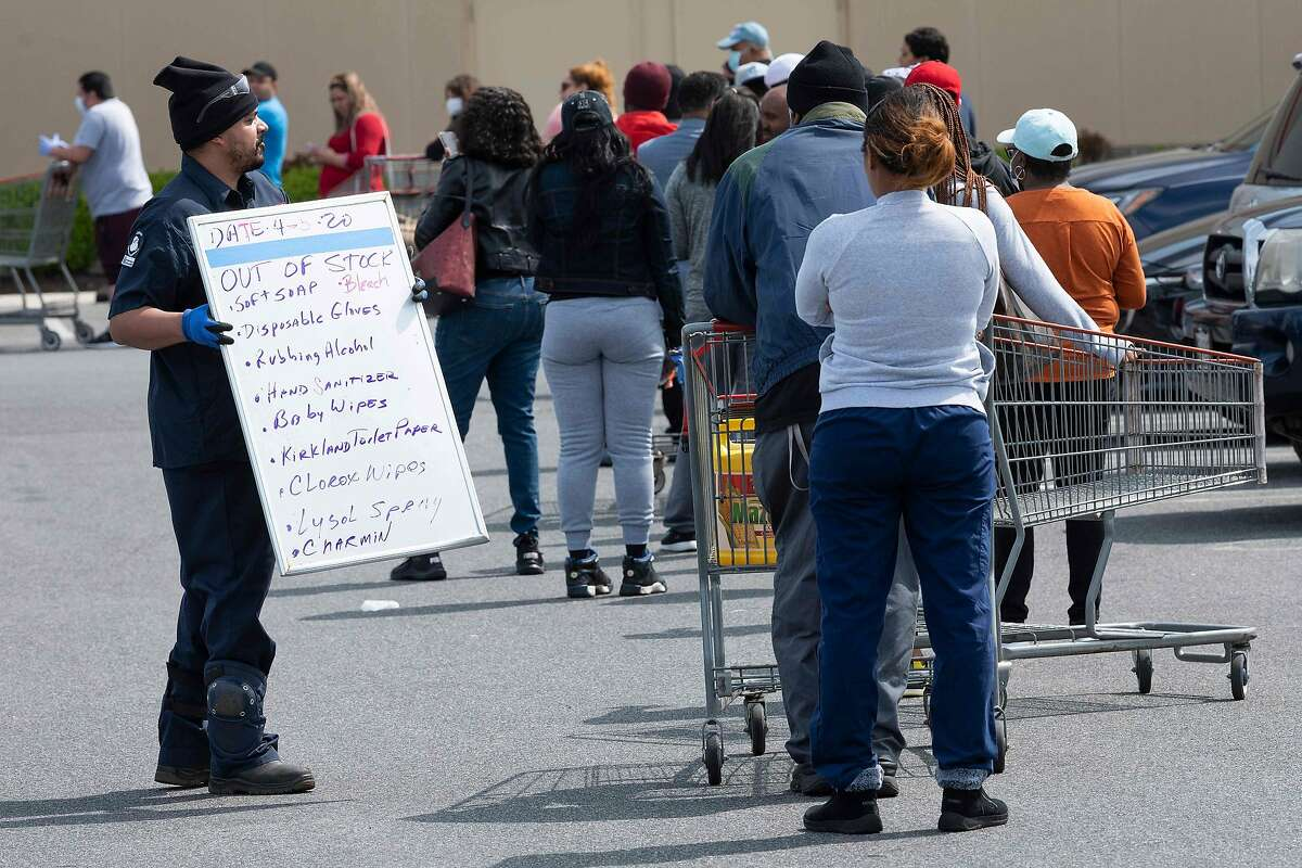A Costco employee holds a sign letting shoppers know what is out of stock as they line up to get into the bulk shopping store in Washington, DC, on April 5, 2020. - The number of confirmed coronavirus, COVID-19, cases in the United States has topped 300,000 and there have been more than 8,100 deaths, Johns Hopkins University reported on Saturday. (Photo by JIM WATSON / AFP) (Photo by JIM WATSON/AFP via Getty Images)