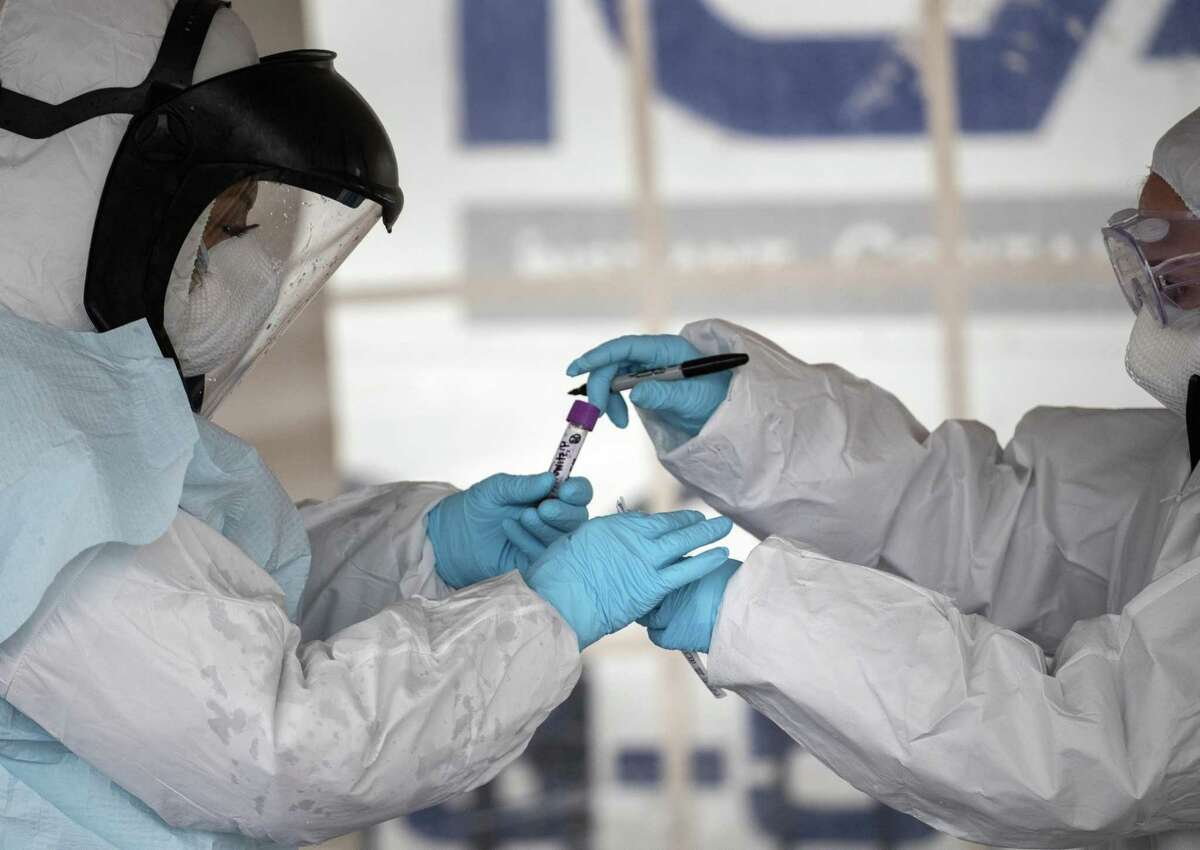 Health workers dressed in personal protective equipment (PPE) handle a coronavirus test at a drive-thru testing station in Stamford, Connecticut.