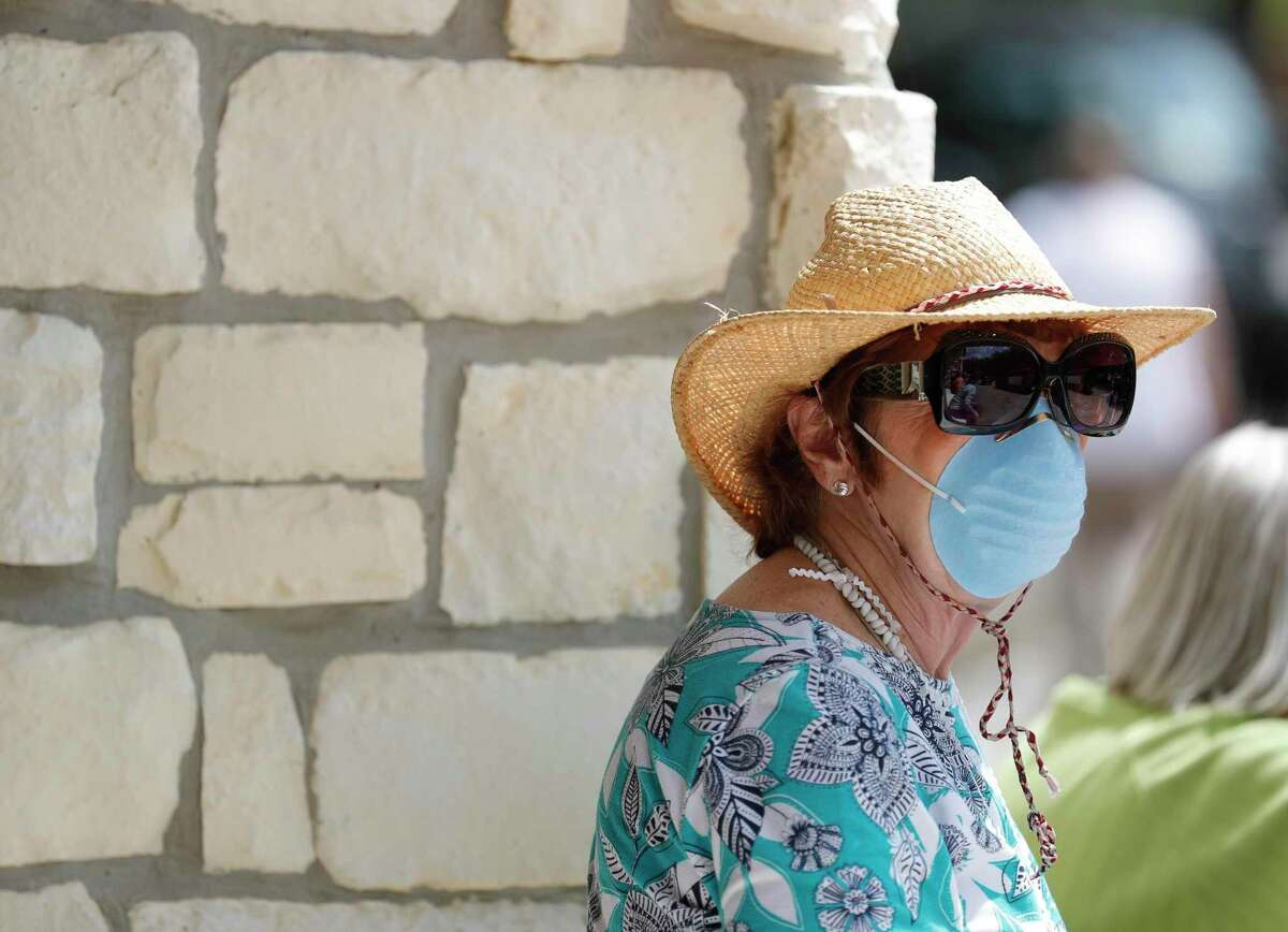 Betty Handley wears a mask as residents of the Carriage Inn Conroe assisted living facility take in a parade from friends, family and other community members, Friday, April 3, 2020, in Conroe. Starting Sunday, April 5, the county began recommending that the general public start wearing face masks while traveling outside.