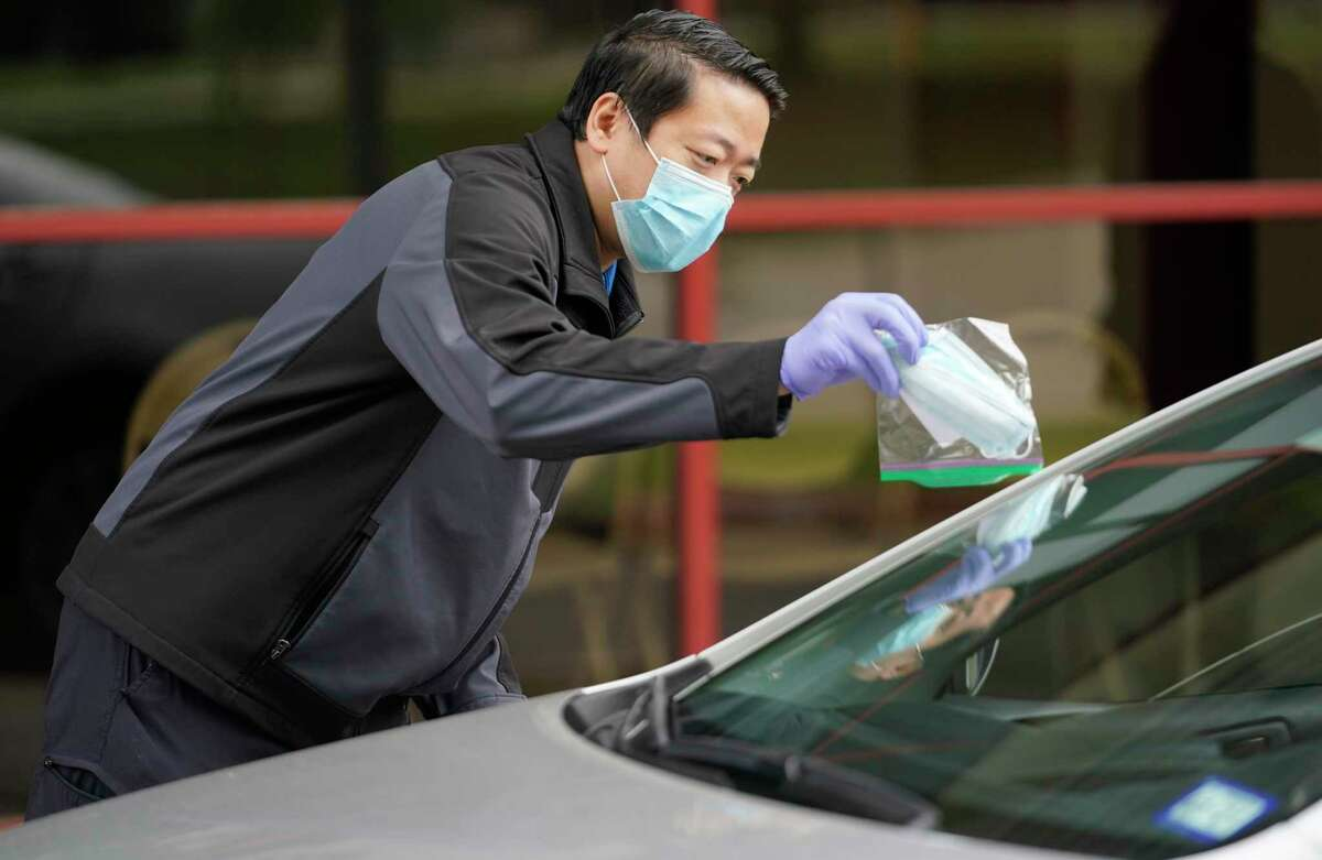 State Rep. Gene Wu hands off a bag containing two surgical masks during a drive-thru handout held at Sharpstown Community Center Sunday, April 5, 2020, in Houston. He had 400 bags each containing two masks to give to healthcare workers, seniors, and individuals with compromised immune systems in his district. The masks were donated by the Sino Professionals Assoc. and the Houston Tsinghua Alumni Assoc.