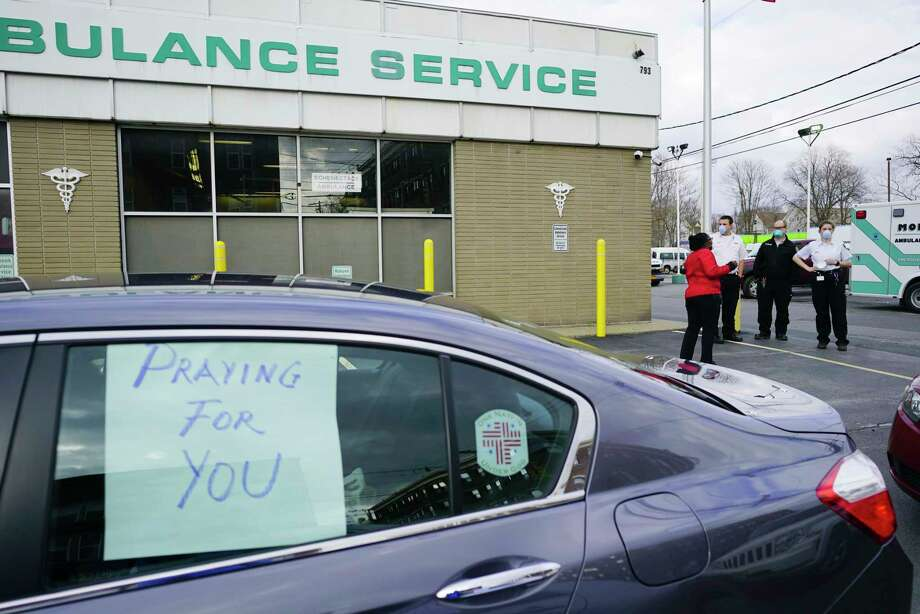 Schenectady City Councilwoman Marion Porterfield, background, speaks with employees of Mohawk Ambulance after prayers were said outside the ambulance garage for the workers and the patients they care for on Sunday, April 5, 2020, in Schenectady, N.Y. A group of religious leaders and members of their congregations along with Schenectady City Councilwoman Marion Porterfield held a vehicle caravan on Sunday visiting first responder locations. At each site one pastor and one member of their congregation got out and prayed.   (Paul Buckowski/Times Union) Photo: Paul Buckowski, Albany Times Union / (Paul Buckowski/Times Union)