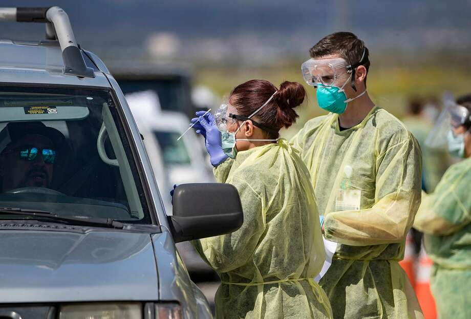 Riverside County medical personnel administer a coronavirus test to a driver at a drive-though testing facility at Diamond Stadium on March 21, 2020 in Lake Elsinore, Calif. The county was approved late in May to enter Phase 2 of California's reopening process, which meant people could head back to malls and dine in at restaurants. (Gina Ferazzi/Los Angeles Times/TNS) Photo: Gina Ferazzi, TNS